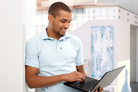 Happy casual afro american man working at home with laptop computer. Smiling, looking at screen, leaning against wall, standing, photo