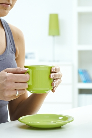 Close up of woman having a cup of tea at home. Holding mug in hand, ring on finger, high key, copyspace. Pastel colors. photo