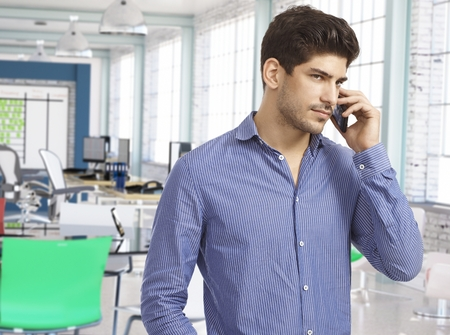 Casual man on the phone at work in modern office. photo
