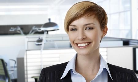 gingerish: Portrait of happy caucasian businesswoman at office.