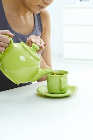 Woman pouring tea from kettle to mug on table. High key bright background, table, pastel colors, close up, indoors home. Copyspace. photo