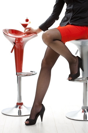 Sexy female legs in black high heels and fishnet stockings, red mini skirt. Holding cocktail drink in bar. White background, sitting on bar stool, close up. Flirting, romance, temptation, fashion, foot, feet. Stock Photo