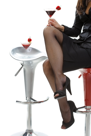 Sexy female legs in black high heels and fishnet stockings, mini skirt. Holding cocktail drink in bar. White background, sitting on bar stool, close up. Flirting, romance, temptation, fashion, foot, feet. Invitation, drink for two. Stock Photo