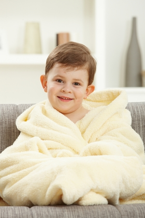 Portrait of happy caucasian kid sitting in oversize bathrobe after taking bath. Smiling, looking at camera, home indoor sofa. photo
