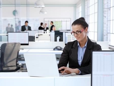 Trustworthy businesswoman working at office desk, using laptop computer.