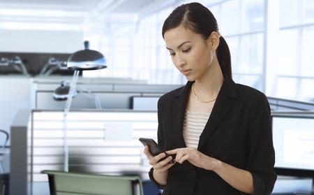 llamando: Empresaria asiática que trabaja en oficina usando el teléfono móvil.
