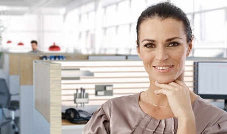 cubicle: Portrait of middle aged female office worker in office cubicle, smiling.