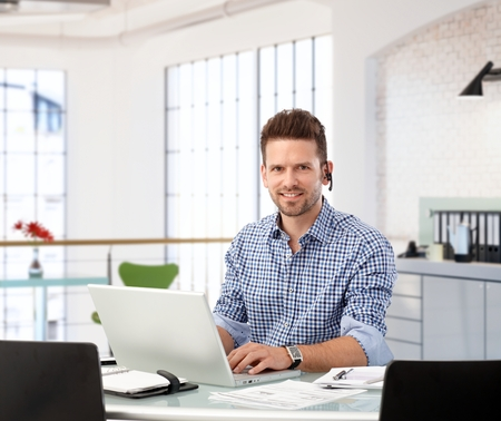 Entrepreneur working with laptop at office desk, looking at camera.
