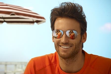 미러 선글라스를 착용 휴일 해변에 행복 잘 생긴 캐주얼 백인 억센 남자, 야외. 선글라스에 여자 친구의 반사를 웃고.