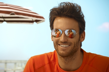 Happy handsome casual caucasian bristly man on holiday beach wearing mirror shades, outdoor. Smiling, girlfriends reflection on sunglasses. Stock Photo