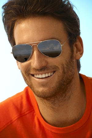 幸せなカジュアルなハンサムな白人伸びた男飛行士サングラス ミラー色合いの肖像画。笑みを浮かべて、完璧な歯。