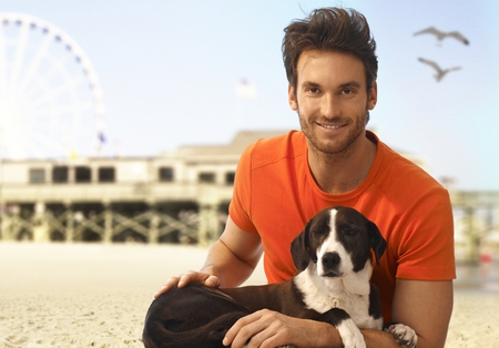 Happy handsome casual caucasian man sitting with dog in his lap at seascape beach. Looking at camera, smiling. Summer holiday, sea, sand.