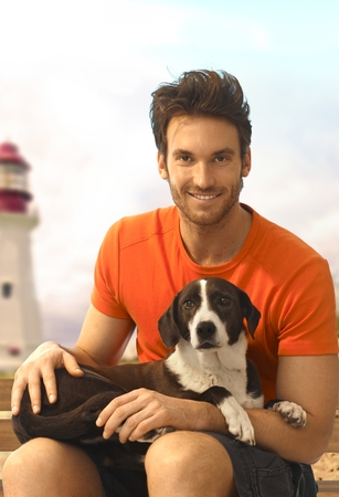 Happy handsome casual caucasian bristly guy sitting with dog laying in lap at the beach. Wearing shorts and t-shirt, looking at camera, smiling. Light tower in background. photo
