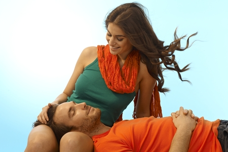 Happy young casual caucasian romantic couple resting with man in lap of girlfriend. Smiling, eyes closed, caressing, relaxing outdoor. Copyspace. Stock Photo