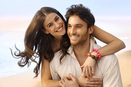 Portrét šťastný, příležitostná, kavkazského manželský pár na pláži. Pohledný muž, atraktivní mladá žena, s úsměvem, díval se na kameru, objala.