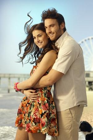 Gelukkig getrouwd kaukasisch paar op huwelijksreis staan en omarmen op zomer vakantie strand. Glimlachen, op zoek in de verte. Stockfoto