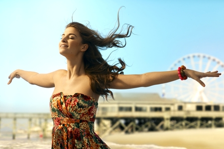 outspreading: Young casual caucasian woman standing eyes closed arms wide open at summer holiday beach. Smiling, dreaming, flying, enjoying freedom. Copyspace.