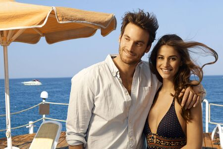 Happy casual caucasian couple standing at at summer sea holiday beach pier. Smiling, looking at camera. Stock Photo - 28105657