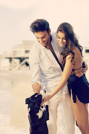 Young casual caucasian dream couple caressing dog at summer beach. Smiling, standing, copyspace. photo