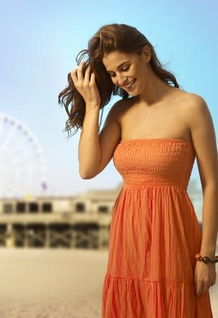 mujer mirando el horizonte: Mujer caucásica joven ocasional feliz de pie en la playa de arena de verano. mirando hacia abajo. Sonreír, copyspace. Foto de archivo