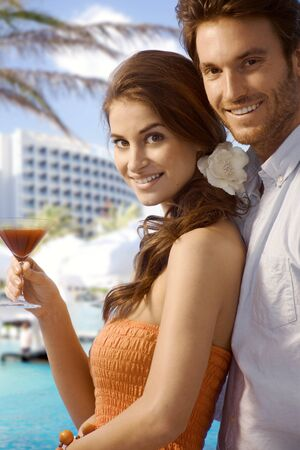 Young happy casual caucasian couple with cocktail drink at luxury summer beach holiday resort. Standing, smiling, looking at camera. Stock Photo - 28105360