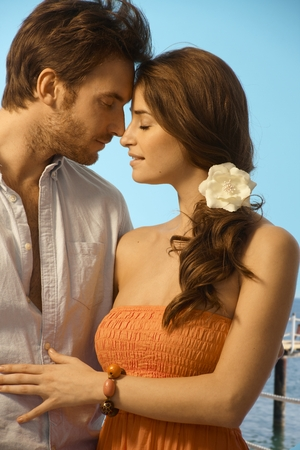 Young attractive casual caucasian couple having a romantic holiday moment at the seaside. Standing, eyes closed, touching, love, romance, flower in hair. Stock Photo - 28105365