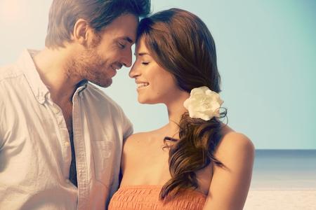 Jonge aantrekkelijke kaukasisch getrouwd paar met een romantisch moment op het zeegezicht strand. Ogen dicht, ontroerend, liefde, romantiek, bloem in het haar.