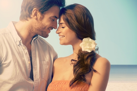 Młoda atrakcyjna dorywczo małżeństwo posiadające romantyczny moment na plaży krajobraz. Oczy zamknięte, wzruszającą, miłość, romans, kwiat we włosach.