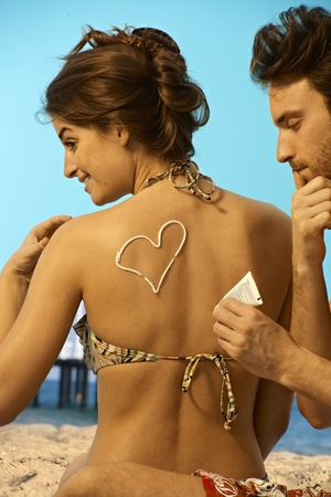 Caucasian man having fun putting sunscreen cream on back of attractive caucasian woman in swimsuit at the beach before sunbathing. Playful, heart sign, sitting. Stock Photo - 28105427