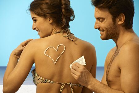 Playful happy young handsome caucasian man putting sun cream on back of woman in swimsuit before sunbathing at the beach. Smiling, having fun, creativity. Stock Photo - 28105441