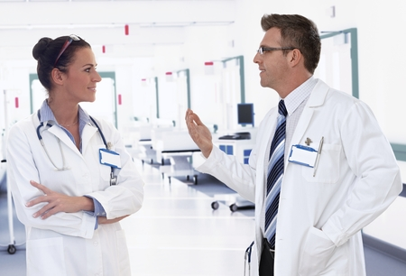 Doctors talking consulting medical situation on hospital corridor. Stock Photo - 28105612
