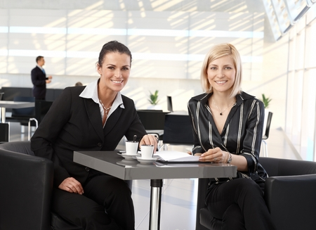 Happy corporate businesswomen meeting at coffee table in office. Stock Photo - 28105026