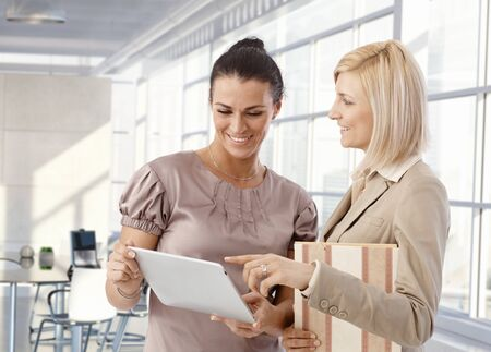 Happy businesswomen at work talking using tablet. photo