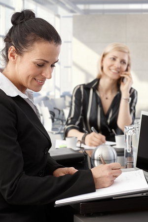 Happy businesswomen working at meeting table in office. Stock Photo - 28105049