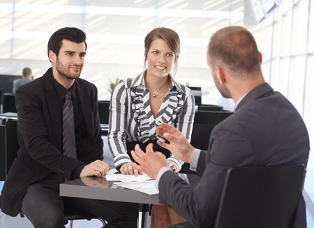 advising: Businesspeople meeting at table in office lobby, talking, smiling.