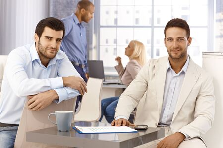 bristly: Portrait of handsome young businessmen sitting by table, looking at camera, smiling. Stock Photo