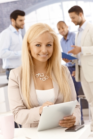 Attractive blonde businesswoman using tablet computer, smiling, looking at camera. photo