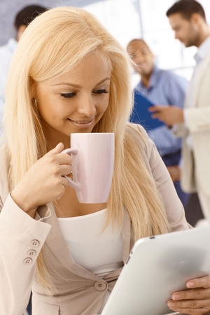 Happy young woman drinking tea, using tablet computer, smiling. photo