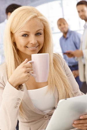 Closeup portrait of attractive young blonde businesswoman drinking tea, using tablet, smiling at camera. photo