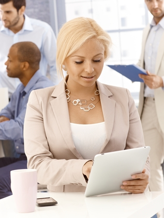 blazer: Closeup portrait of blonde businesswoman sitting at desk, using tablet computer.