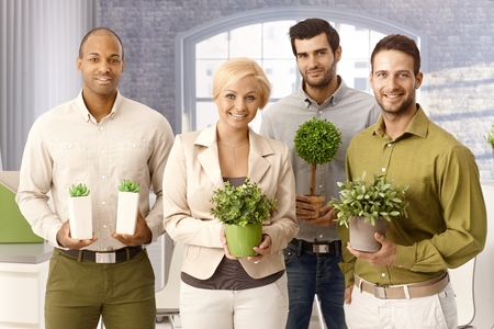 green clothes: Happy environment friendly businessteam smiling, holding green plants, looking at camera.