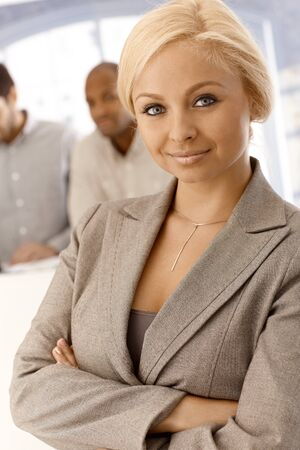 Closeup portrait of confident young businesswoman standing arms crossed, looking at camera. photo