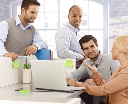 Three businessmen and a businesswoman working together in office, using laptop computer.
