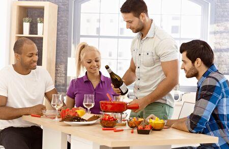compa�erismo: Compa�erismo joven que tiene fondue de queso en casa en buen estado de �nimo, la sonrisa, hablando, bebiendo vino. Foto de archivo