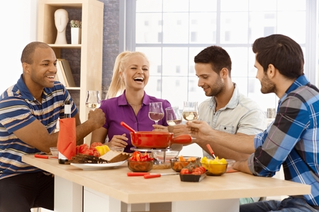 Gelukkig gezelschap zitten rond tafel thuis, met kaasfondue, klinkende glazen. Stockfoto