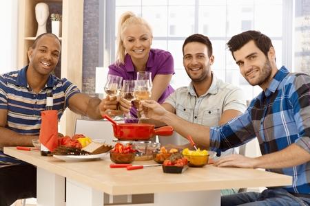 compa�erismo: Compa��a joven y feliz tintineo de vasos alrededor de la mesa de la cena, sonriente, mirando a la c�mara.