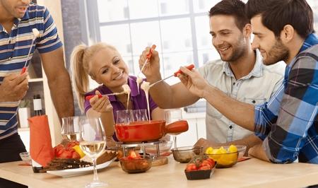 Gelukkige vrienden genieten van tijd samen, met kaasfondue, glimlachend. Stockfoto
