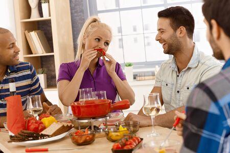 compa�erismo: Compa�erismo feliz disfrutando de la cena juntos, chica formando bigote de la pimienta dulce. Foto de archivo