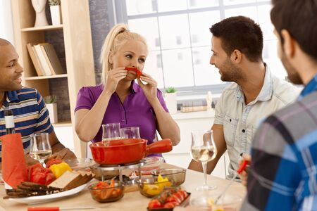 companionship: Happy companionship having dinner together, woman forming moustache from sweet pepper, having fun. Stock Photo