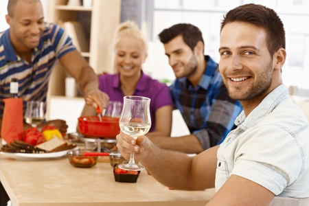 room mate: Young man having dinner party with friends, smiling, drinking wine, looking at camera.
